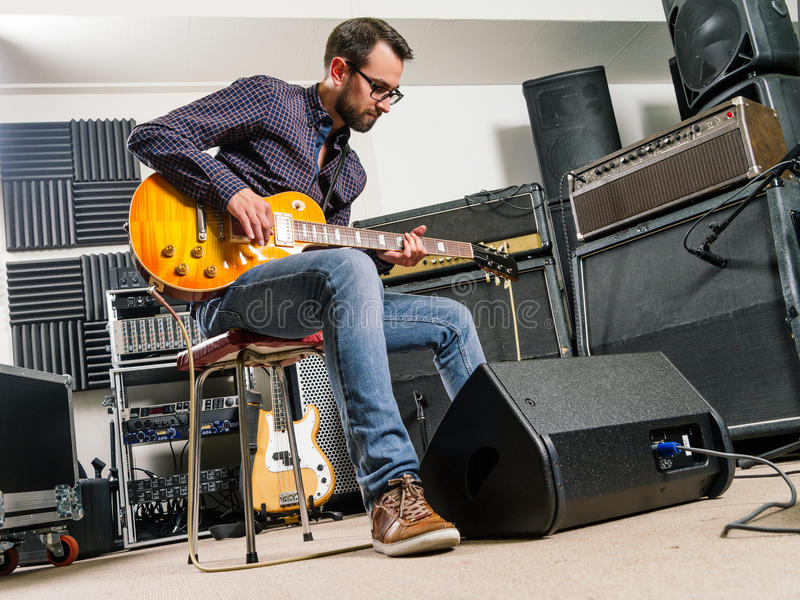 Tocar la guitarra eléctrica en un estudio foto de archivo libre de regalías