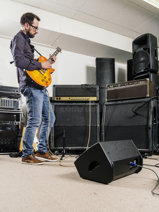 Tocar la guitarra en el estudio de grabación fotografía de archivo libre de regalías