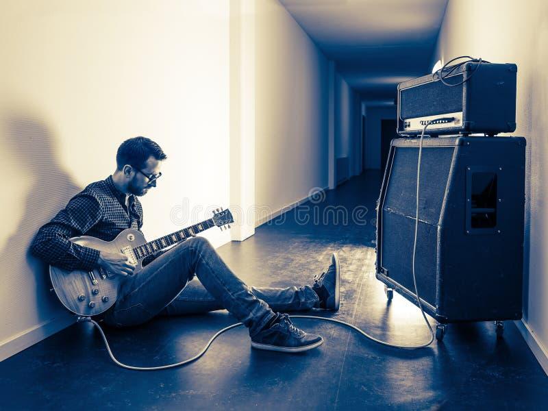 Tocar su guitarra eléctrica en el vestíbulo fotografía de archivo libre de regalías