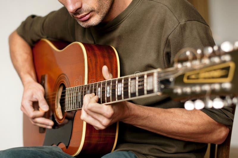 Tocar una guitarra acústica de doce cadenas imagen de archivo libre de regalías