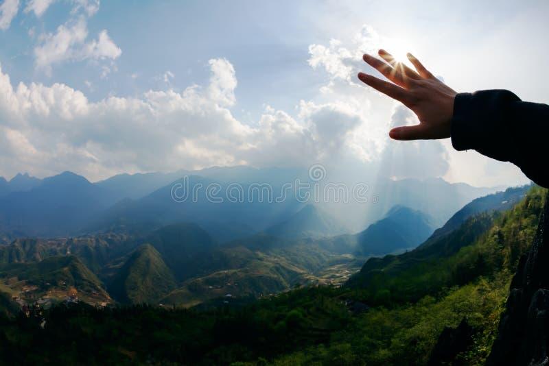 Tocco al sole Mano che tocca il cielo con il raggio fotografia stock