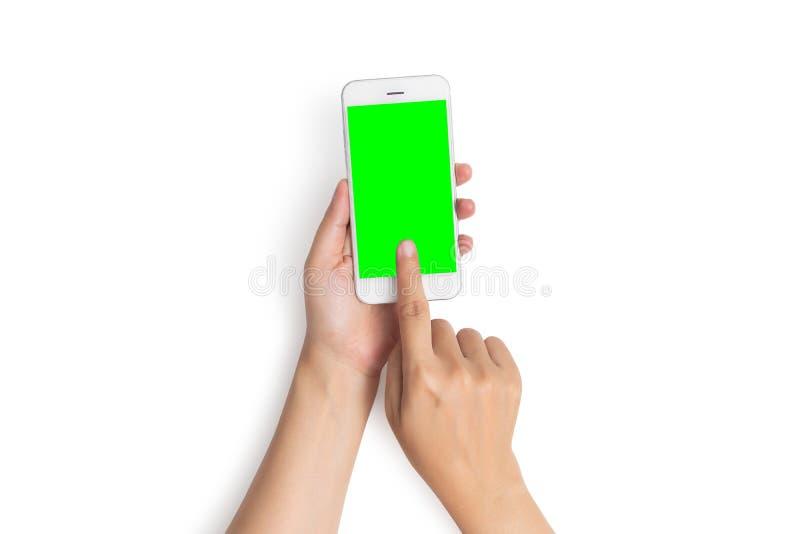 Tocco del dito di uso della mano della donna sul bottone del telefono cellulare con lo schermo verde in bianco dalla vista superi immagine stock libera da diritti