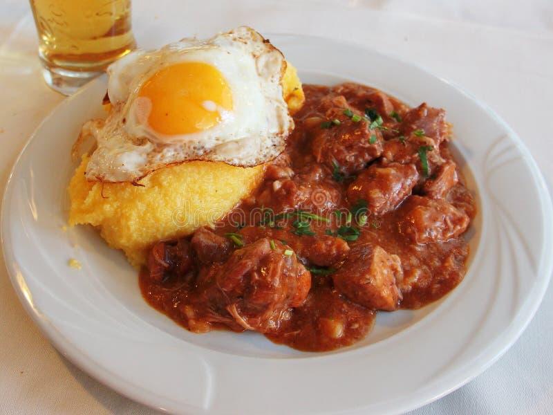 Tochitura tjänade som den traditionella rumänska maträtten som gjordes med nötkött och griskött, med ägg och polenta royaltyfria bilder