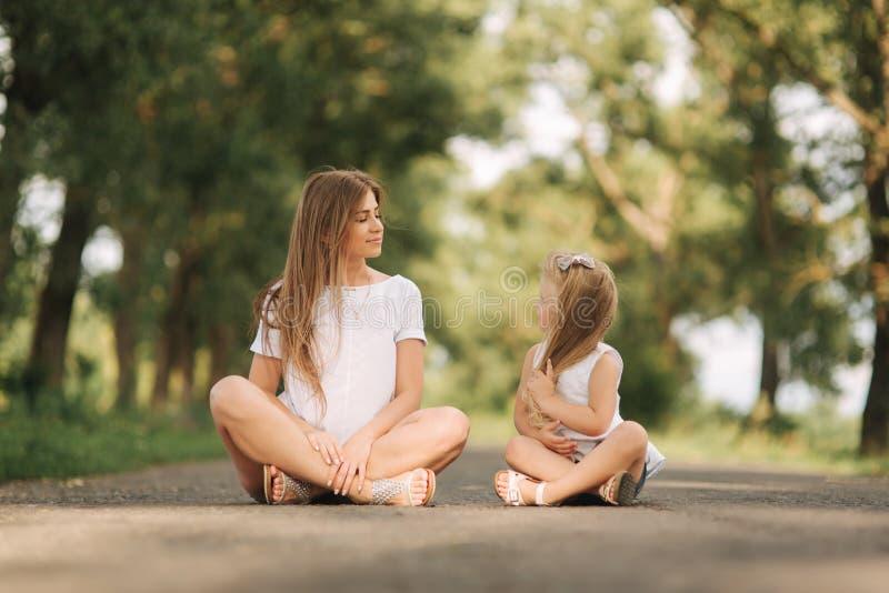 Tochter der attraktiven Mutter und des blonden Haares sitzt auf Straße nahe großer Gasse Sie lächeln und schauen zum natune stockfoto
