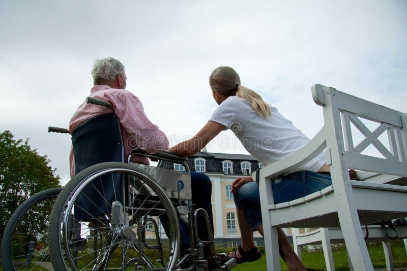 Tochter der jungen Frau mit älterem Vater im Rollstuhl am Krankenpflegeruhesitz lizenzfreies stockfoto
