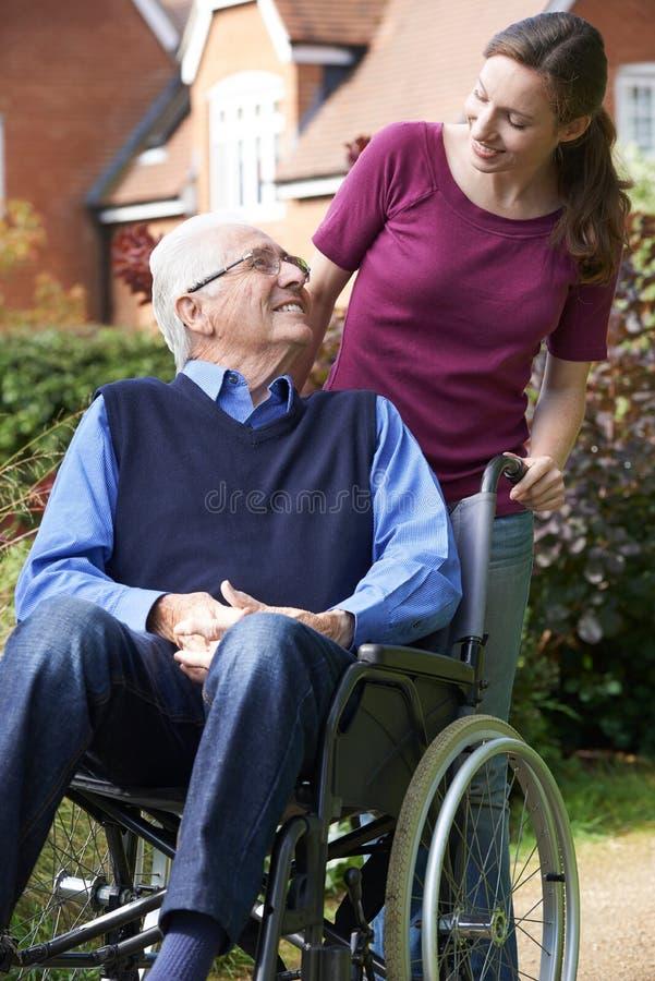 Tochter, die älteren Vater In Wheelchair drückt stockfotografie