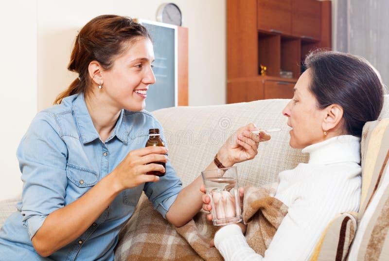 Tochter, die der reifen Frau den flüssigen Medikament gibt lizenzfreies stockfoto