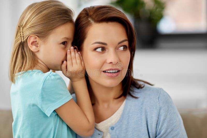 Tochter, die Geheimnis fl?stert, um zu Hause zu bemuttern lizenzfreies stockbild