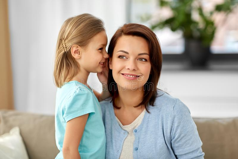 Tochter, die Geheimnis fl?stert, um zu Hause zu bemuttern stockbilder