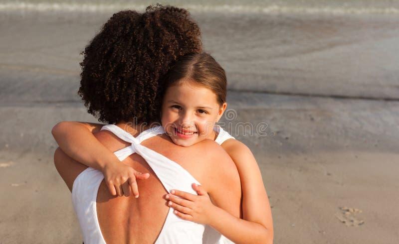 Tochter, die ihre Mutter auf dem Strand umarmt lizenzfreies stockbild