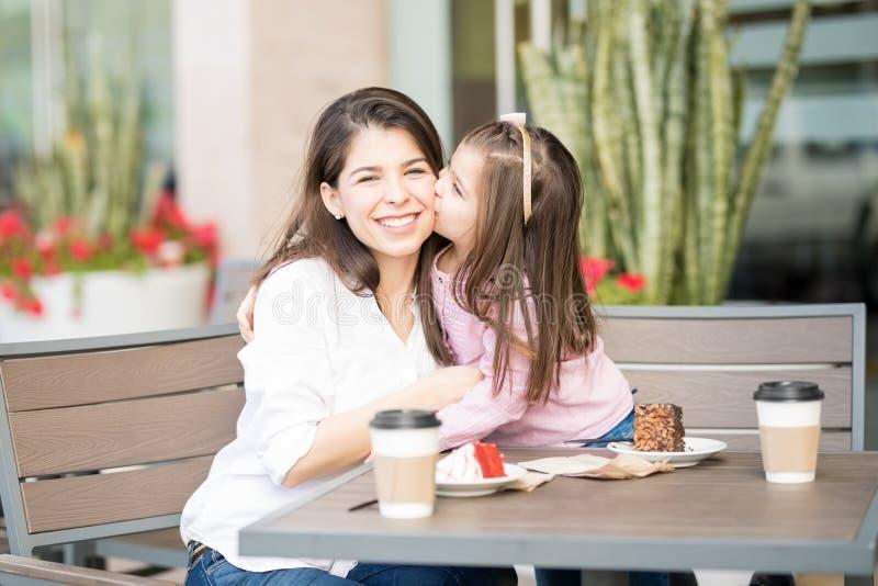 Tochter, die ihre Mutter am Café küsst stockbild