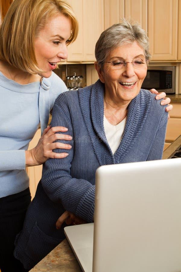 Tochter, die ihrer Mutter auf dem Computer hilft lizenzfreie stockbilder