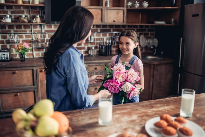 Tochter, die ihrer Mutter einen Blumenstrauß von Pfingstrosen gibt lizenzfreie stockfotografie