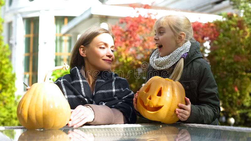 Tochter, die Kürbissteckfassung-olaterne holt, um zu bemuttern, Vorbereitung für Halloween stockbild