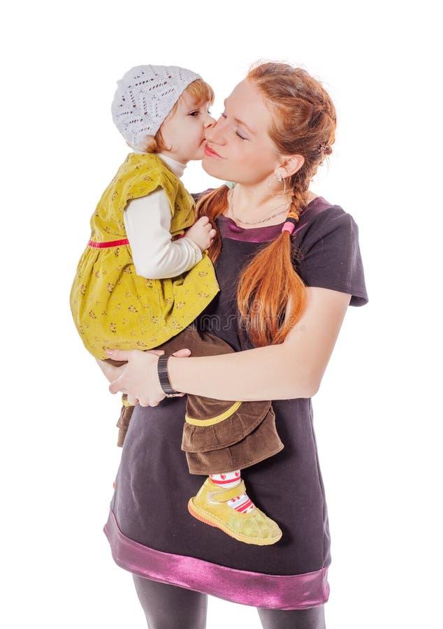 Tochter, die Mutter küsst stockfotos