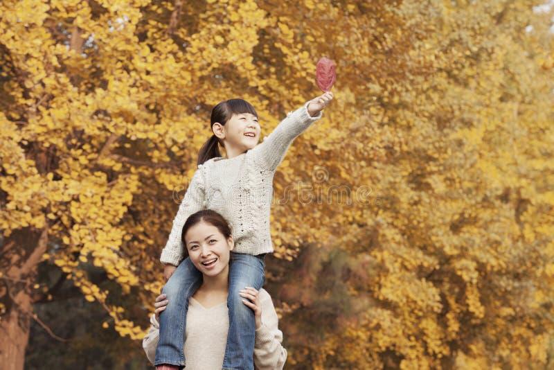 Tochter, die Piggyback auf die Schultern der Mutter genießen Autumn Leaves fährt stockfotos