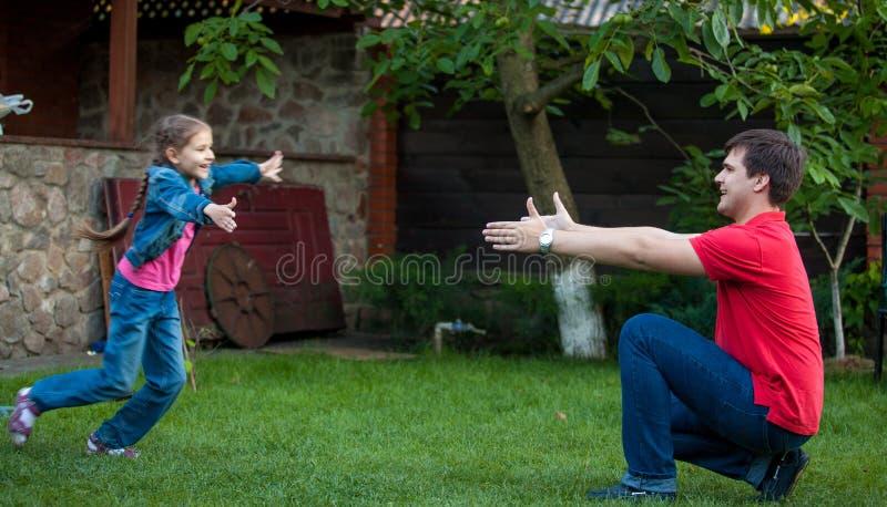 Tochter, die am Vater läuft, um ihn am Park zu umarmen lizenzfreie stockbilder