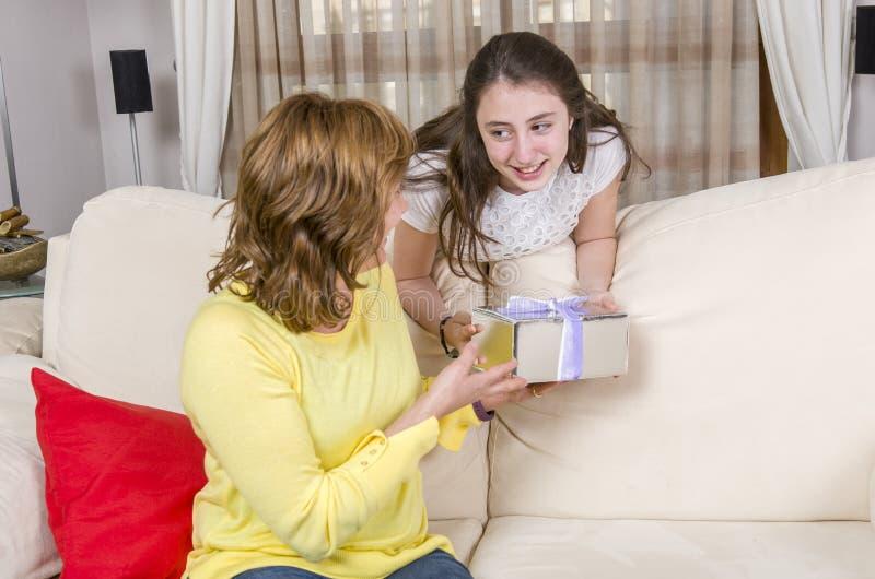 Tochter gibt einem Geschenk ihre Mutter am Mutter ` s Tag stockbilder