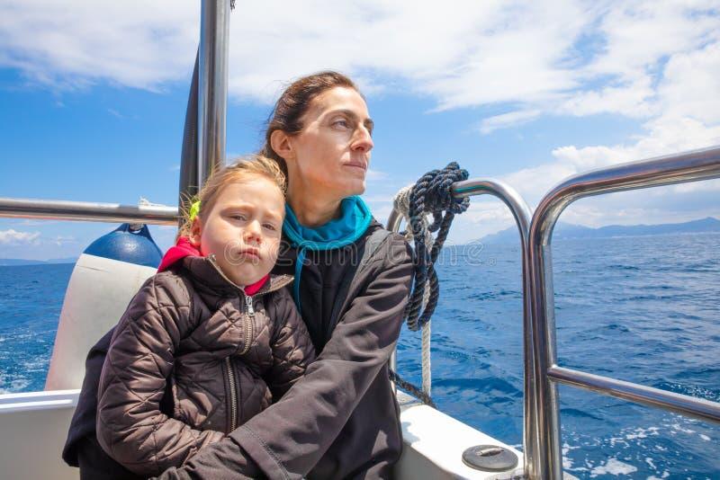 Tochter mit Abneigungsgesichtsausdruck mit Mutter im Motorboot stockbild
