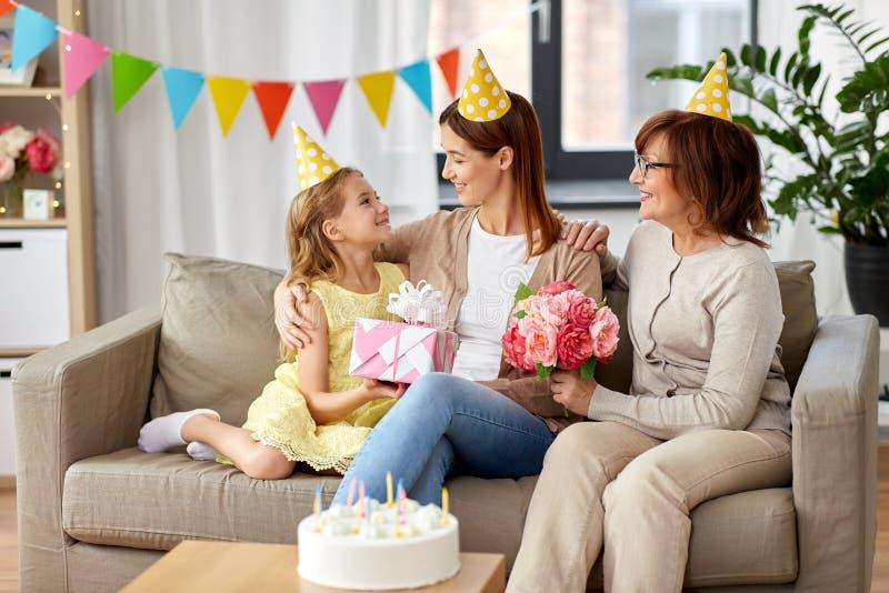 Tochter mit Geschenkboxgrußmutter auf Geburtstag stockfotografie