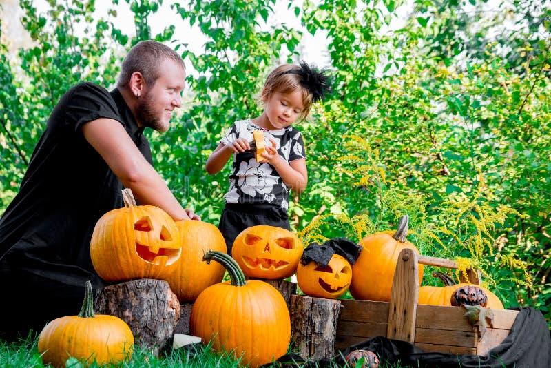 Tochter nahe Vater, der Samen und Faserstoff von einem Kürbis zieht, bevor es für Halloween schnitzt Bereitet Steckfassung-Olater stockfotografie
