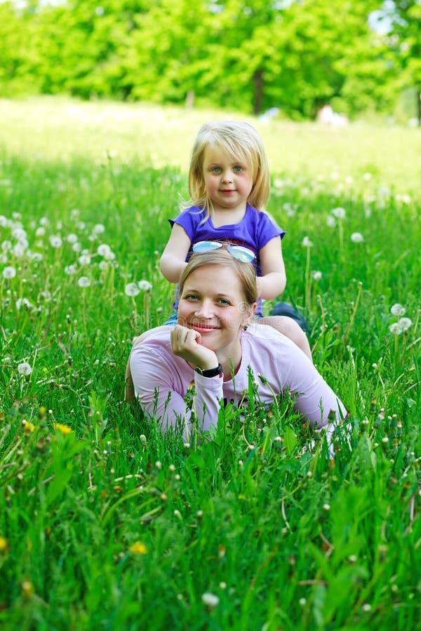 Tochter sitzt auf Mutter auf einem Gras draußen stockbild
