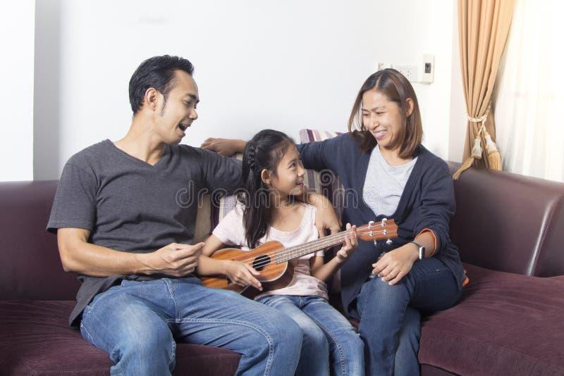 Tochter-Spielukulele der glücklichen Familie unterrichtende lizenzfreie stockbilder
