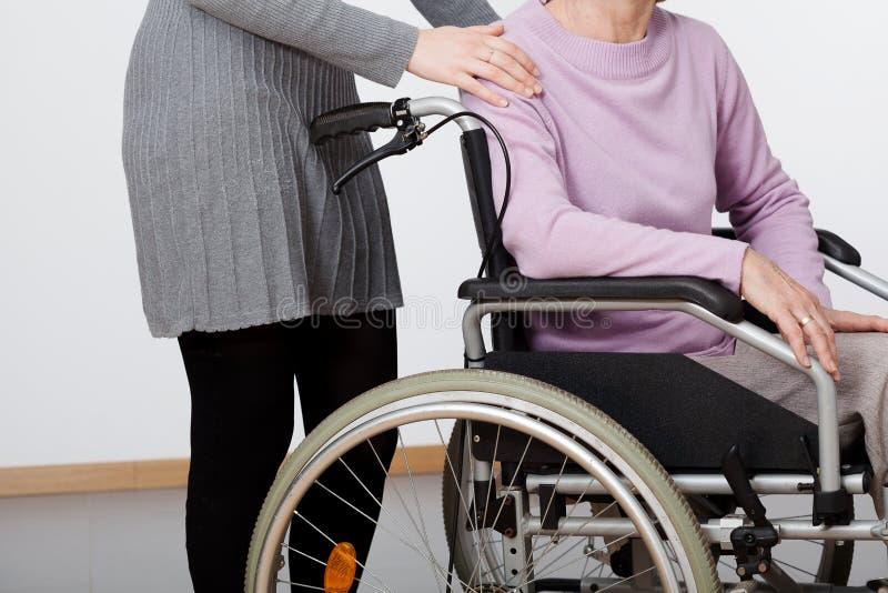Tochter und ihre Mutter auf Rollstuhl stockfoto