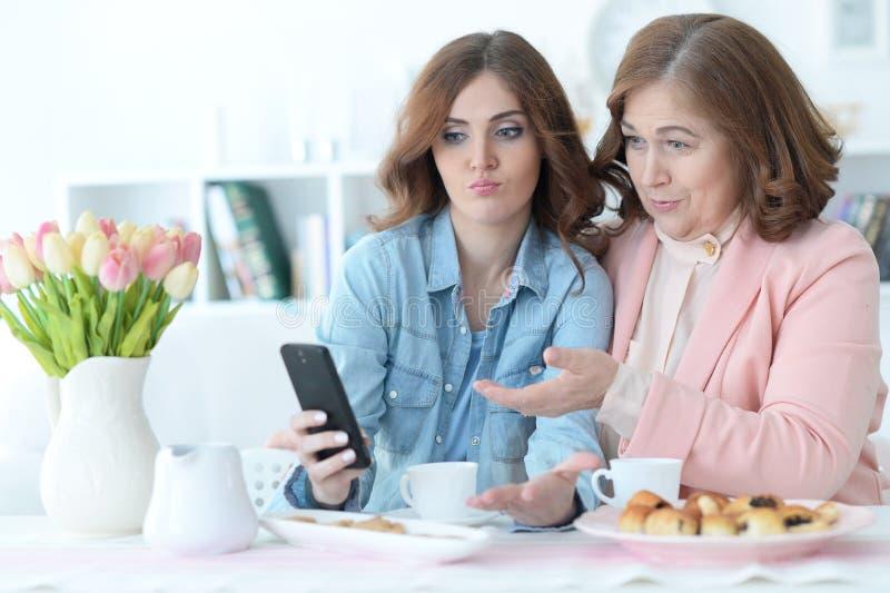 Tochter unterrichtet eine ältere Mutter, einen Handy zu benutzen stockfotografie