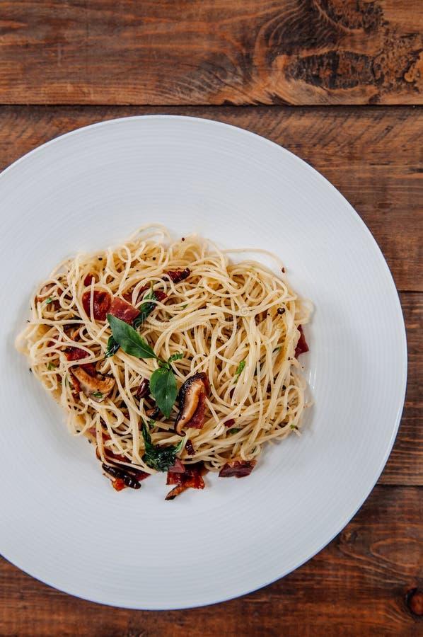 Tocino de las pastas de los espaguetis con los chiles picantes secados en la placa blanca encendido foto de archivo