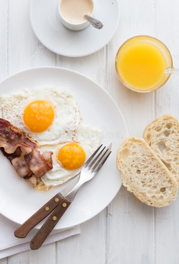 Tocino y huevos Huevos fritos del estilo rural del desayuno con las tiras del jamón del cerdo Endecha plana imagen de archivo