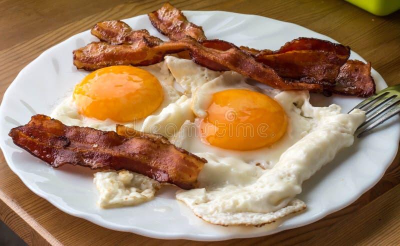 Tocino y huevos Huevos fritos del estilo rural del desayuno con el jamón del cerdo fotos de archivo