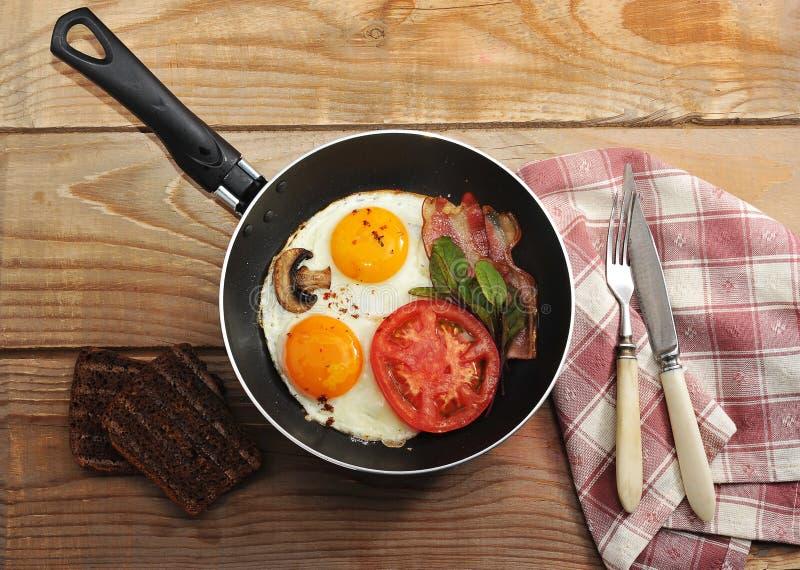 Tocino y huevos y setas con la cacerola en el fondo de madera i imagen de archivo