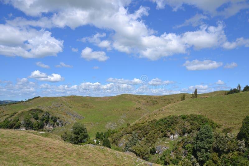 Toczni wzgórza i chmurni niebieskie nieba zdjęcie stock