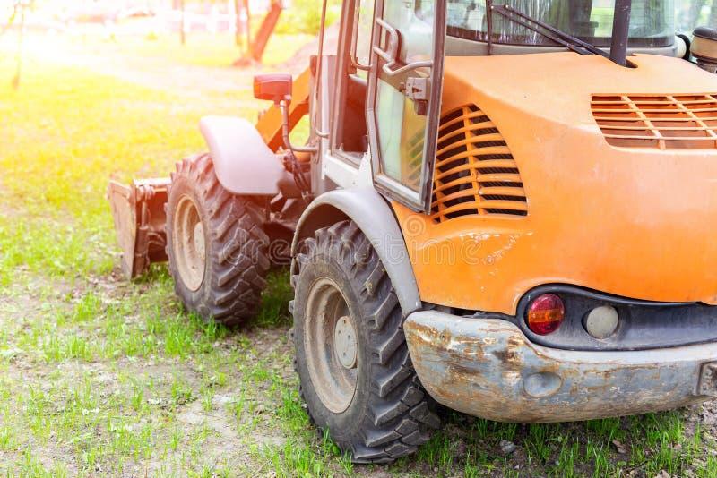 Toczy ładowacz maszynę na trawy polu w parkowym terenie Miejskie pracy na odbudowy i odnowienia miasta rekreacyjnym terenie Ciężk obrazy royalty free