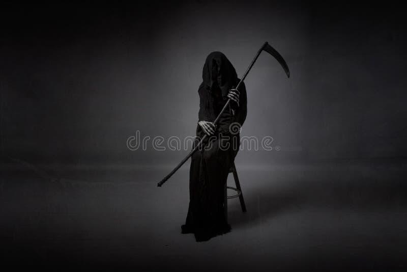 Tod, der an Hand mit den Armen sitzt stockfotos