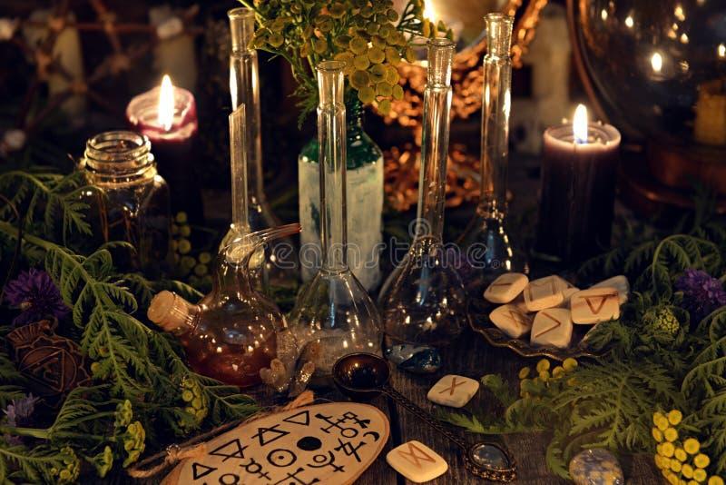 Todavía de la alquimia vida con las botellas y frasco de cristal, runas, hierbas curativas y objetos rituales foto de archivo