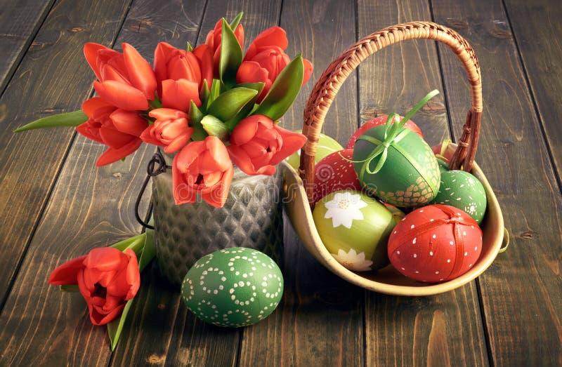 Todavía de Pascua vida Tulipanes rojos y una cesta de este rojo y verde imagen de archivo