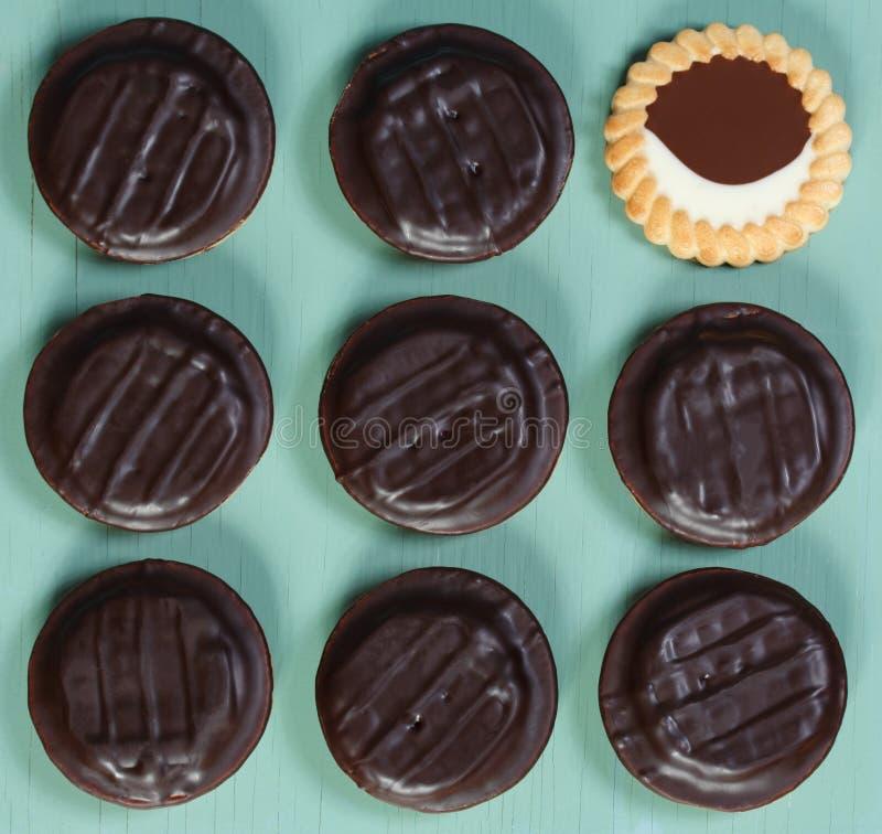 Todavía del arte pop vida Galletas cubiertas con el esmalte oscuro del chocolate fotos de archivo