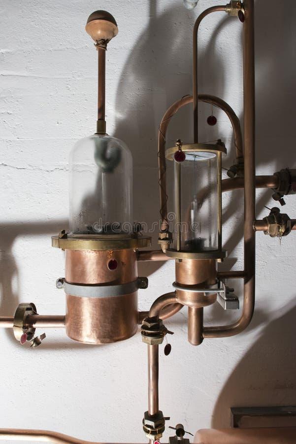 Todavía del cobre alambique dentro de la destilería fotos de archivo