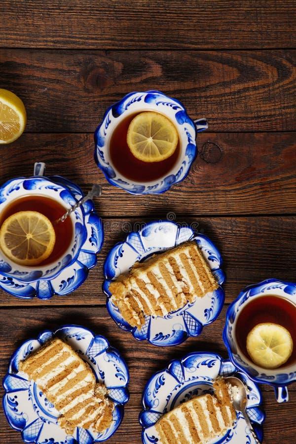 Todavía del día de fiesta vida Placas con los pedazos de torta y de tazas sabrosas de té con el limón en fondo de madera del grun imagen de archivo