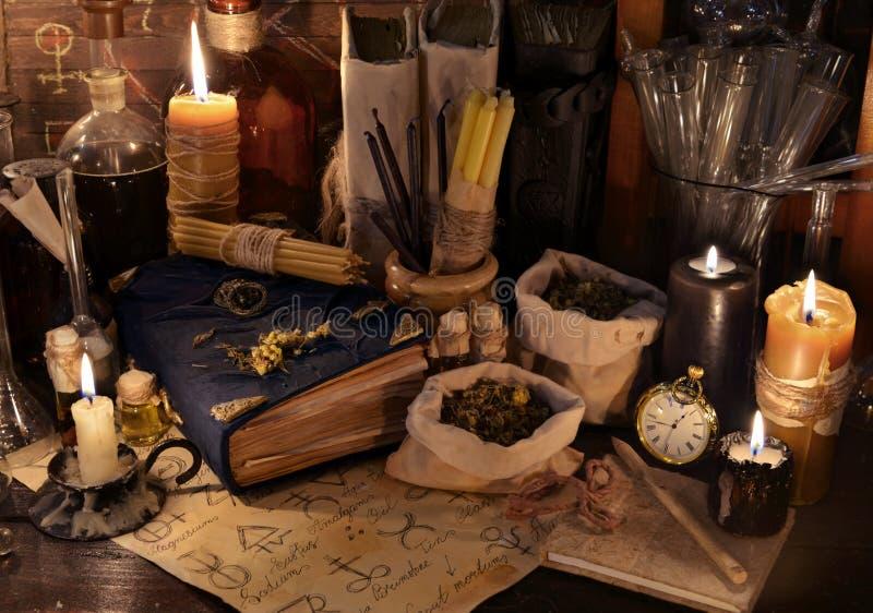 Todavía del místico vida con las hierbas curativas, las velas y los libros de la magia fotografía de archivo libre de regalías