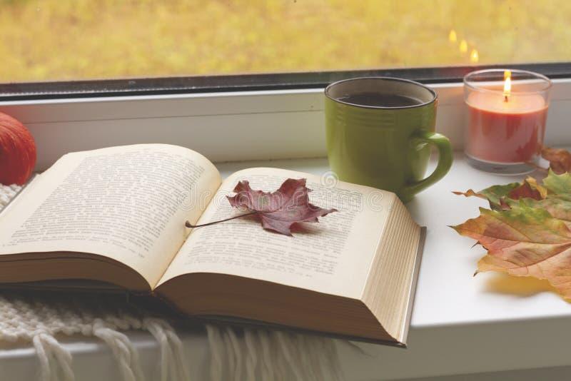 Todavía del otoño vida libros, hojas, taza y palmatoria en ventana fotografía de archivo libre de regalías