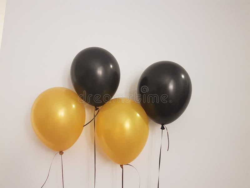 Todavía del primer la imagen del oro decorativo y el helio negro hinchan fotografía de archivo