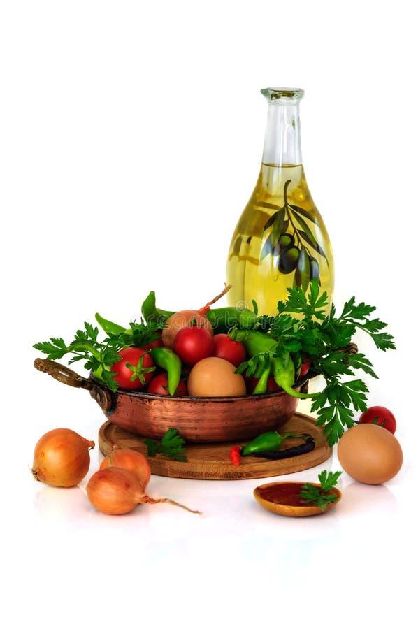 Todavía del primer vida con las verduras mezcladas en sartén, huevos y el aceite de oliva aislado en el fondo blanco foto de archivo libre de regalías