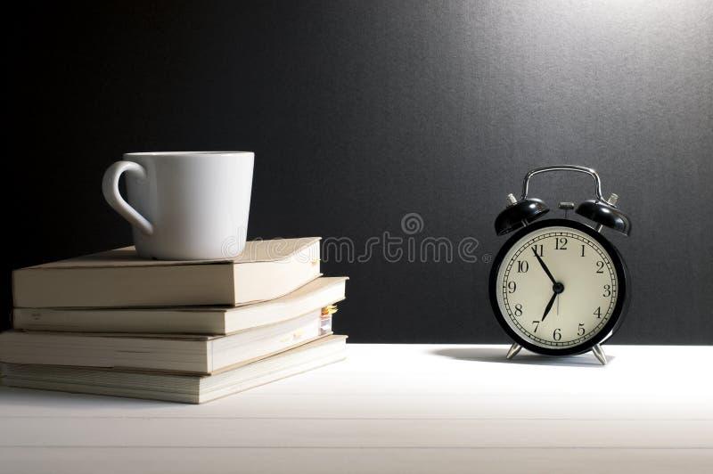 Todavía despertador retro de la vida, taza de café en los libros viejos fotografía de archivo libre de regalías