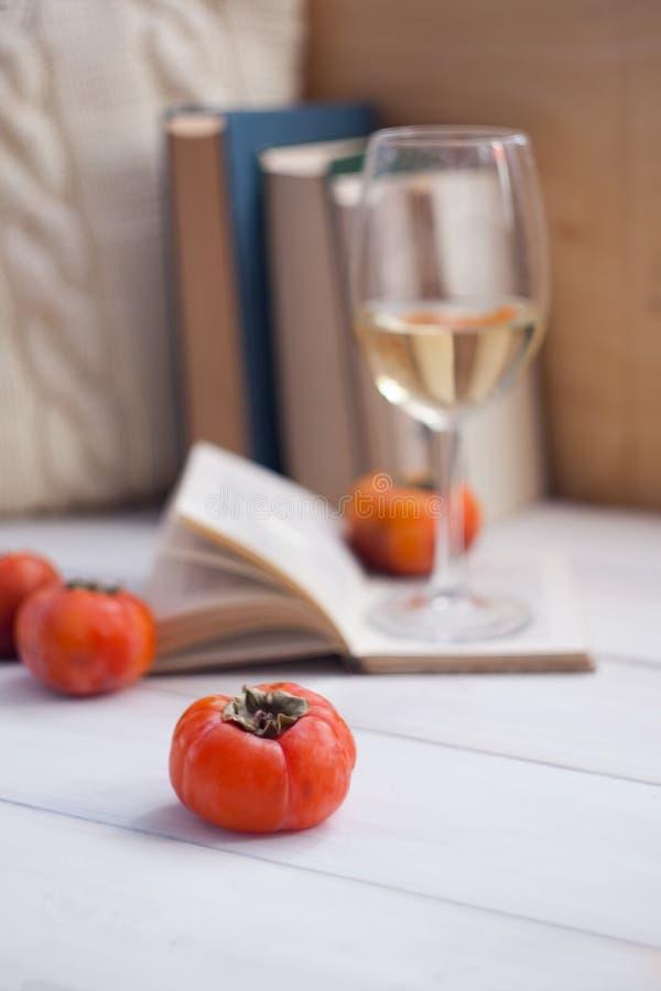 Todavía detalles, libros, vidrio de vino y frutas de la vida en la tabla de madera del vintage retro en sala de estar Fin de sema imágenes de archivo libres de regalías