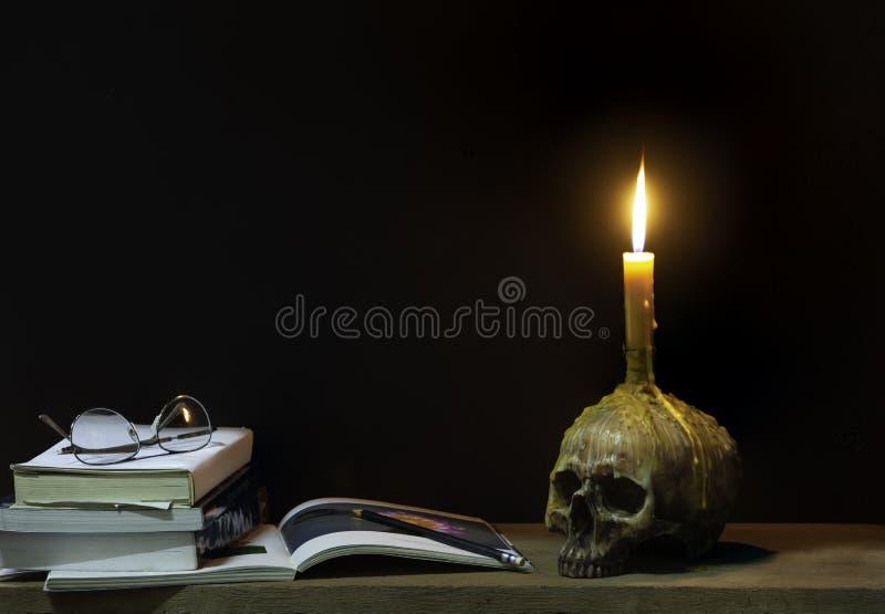 Todavía estilo de vida; Cráneo y lentes de la palmatoria en los libros, lápices en el tablón de madera foto de archivo