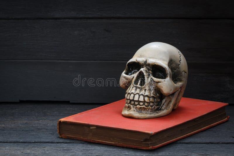 Todavía fotografía de la vida con el cráneo y el libro humanos en el backgr de madera imágenes de archivo libres de regalías
