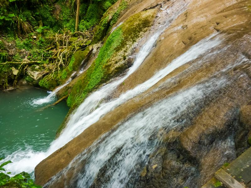 Todavía hermoso, incluso con flujo reducido en la caída temprana, se derrama a través y conecta en cascada sobre un acantilado cu foto de archivo libre de regalías